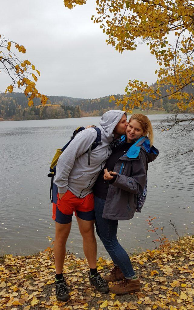 Para całująca się nad jeziorem, otoczona spadającymi liśćmi z jesiennych drzew.