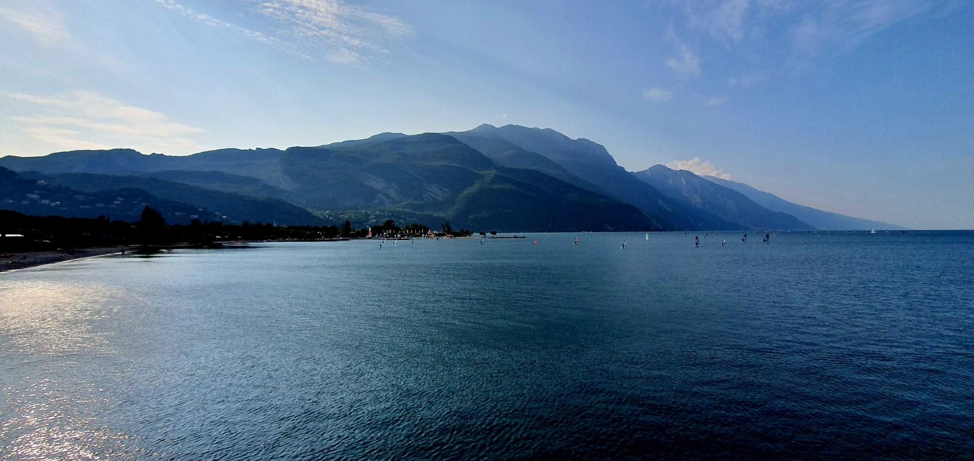 Jezioro Garda, tłum windsurferów z górami w tle w słoneczny dzień.