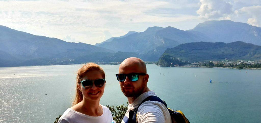 Para w ciemnych okularach nad jeziorem Garda w słoneczny dzień.