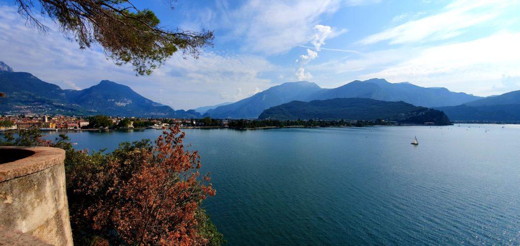 Panorama Jeziora Garda, żaglówka na spokojnym jeziorze.
