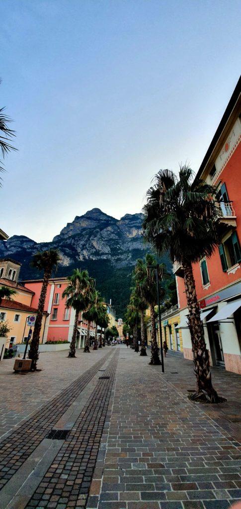 Bezludna uliczka w Riva del Garda Palny, kolorowe kamieniczki i góry w tle.