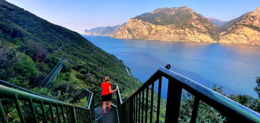 Dziewczyna na zielonych schody nad Jeziorem Garda. ścieżka widokowa.