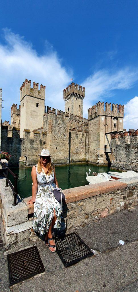 Dziewczyna w kaeluszu i letniej sukience siedząca na murku, przy zamku w Sirmione.