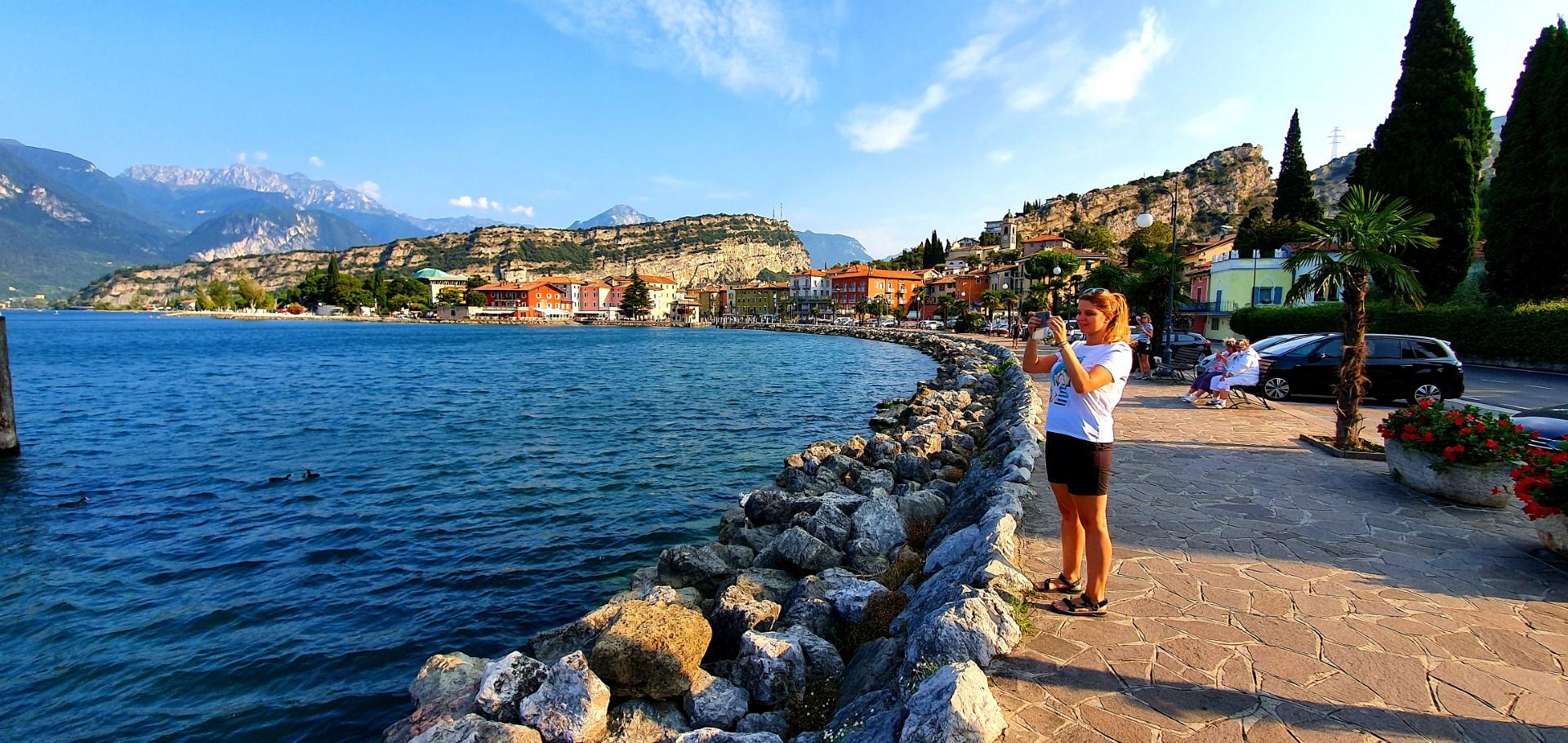 Dziewczyna robiąca zdjęcie nad brzegiem Jeziora Garda. Widok na Torbole sul Garda.