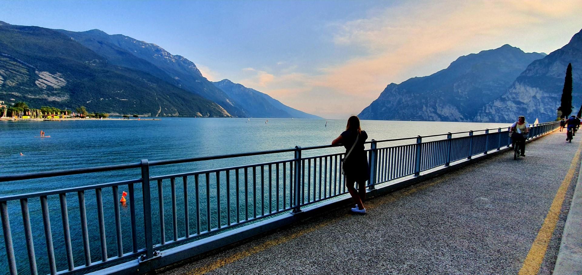 Dziewczyna w sukience, opierająca się o barierkę podziwiająca Jezioro Garda.