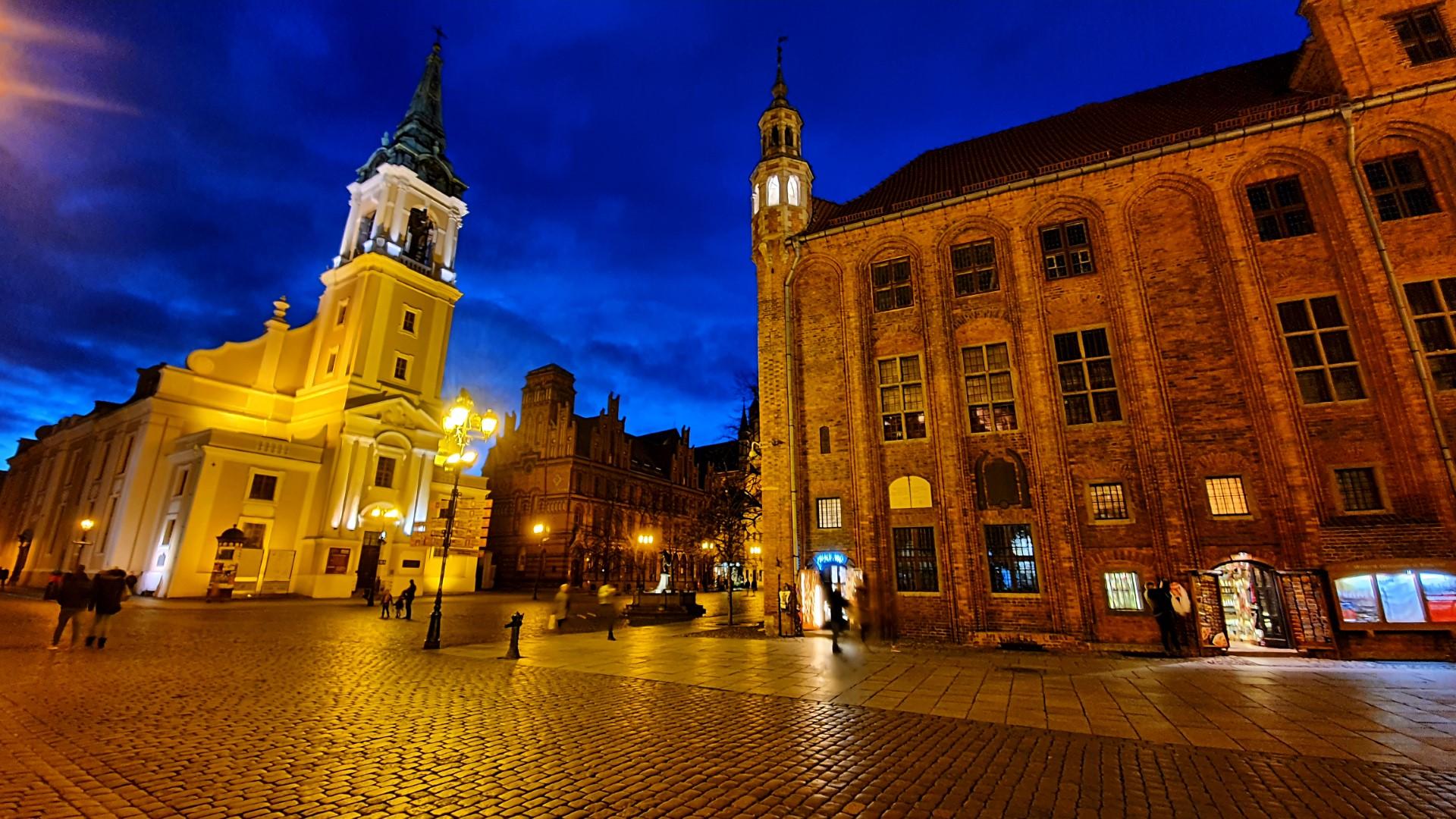 Widok starówki w Toruniu nocą ładnie oświetlony ratusz