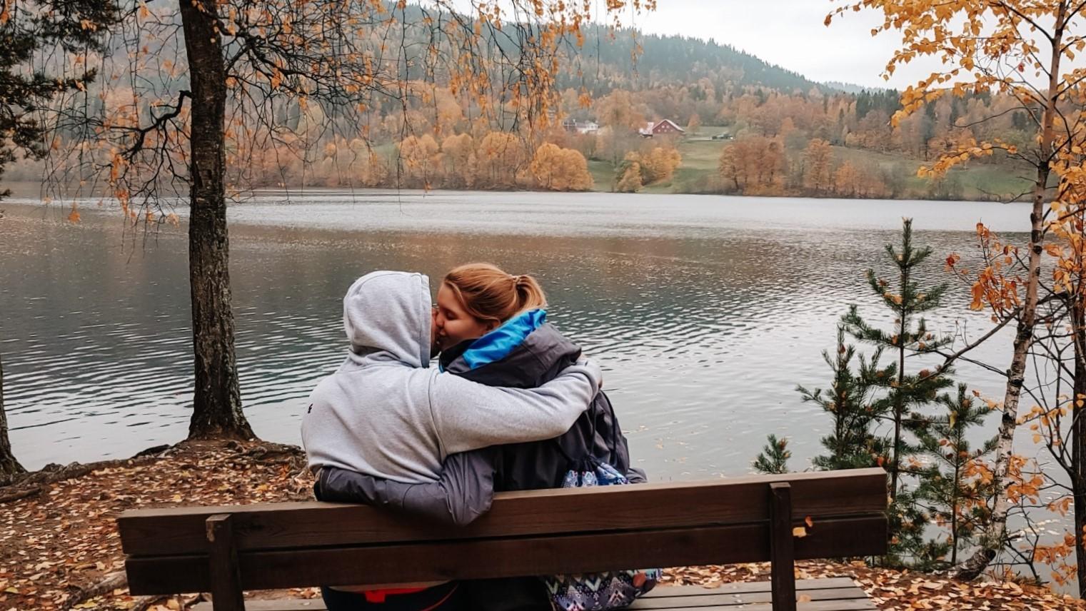 Para całująca się na tle jeziora w jesiennych kolorach.