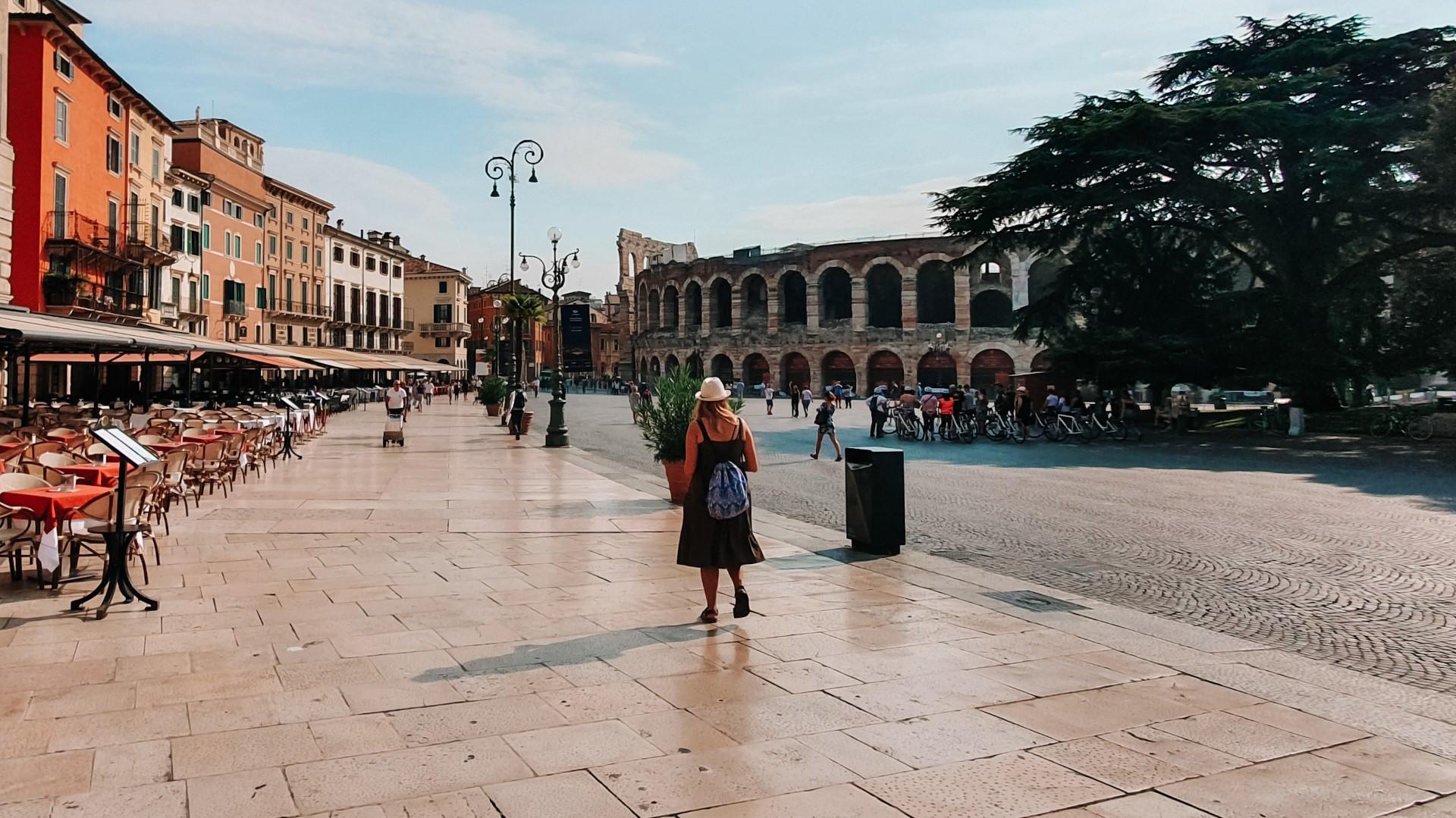 Osłoneczniony plac i zabytkowe kamienice obok areny werona