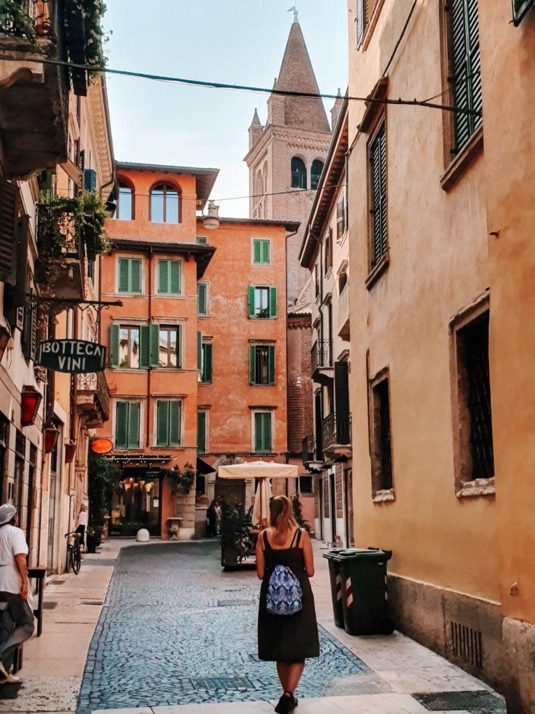 Dziewczyna z plecakiem wsukience przechadza się ulica Werony.