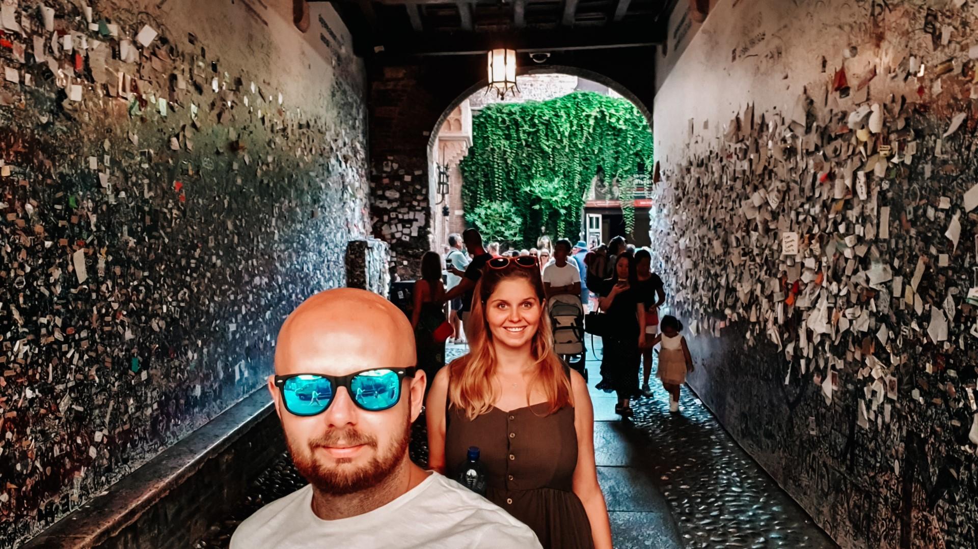 Para w przejściu do domu Julii w Weronie, ściany obwieszone listami.