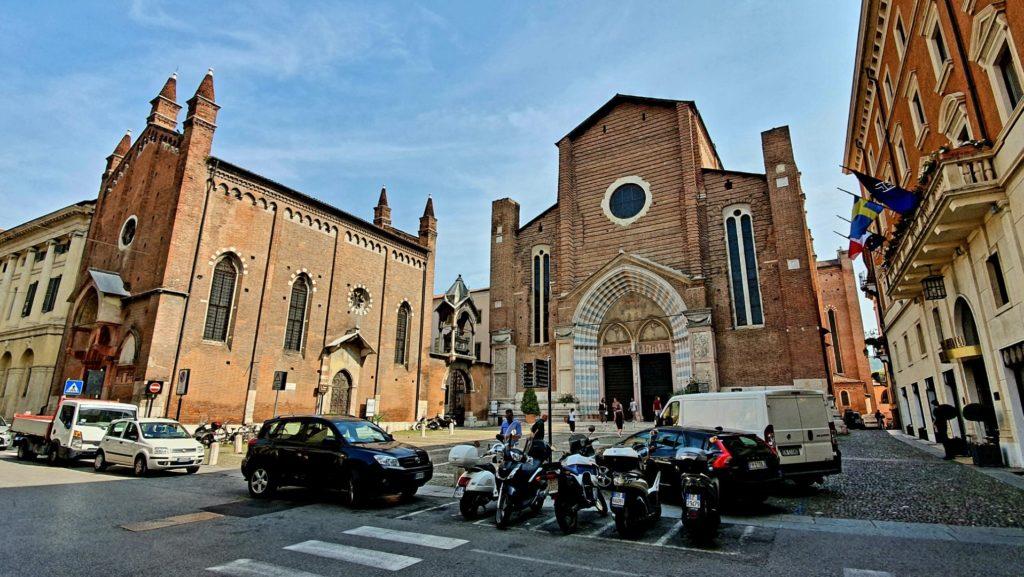 Ulica i zaparkowane skutery przed kościołem w Weronie.