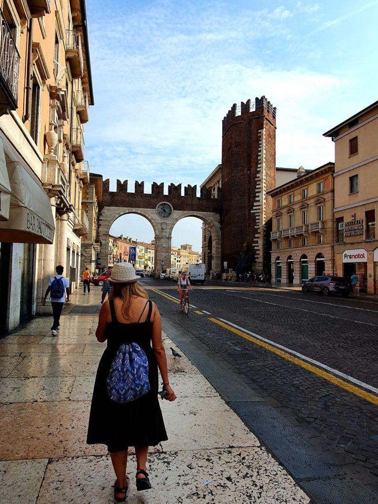 Dziewczyna w kapeluszu i sukience przechadza się ulica Werony.