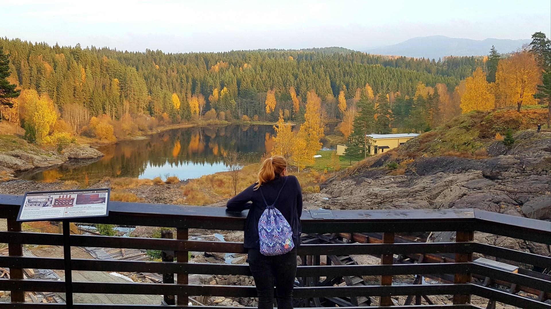 Dziewczyna stojąca przy barierce i podziwiająca piękne jesienne widoki.
