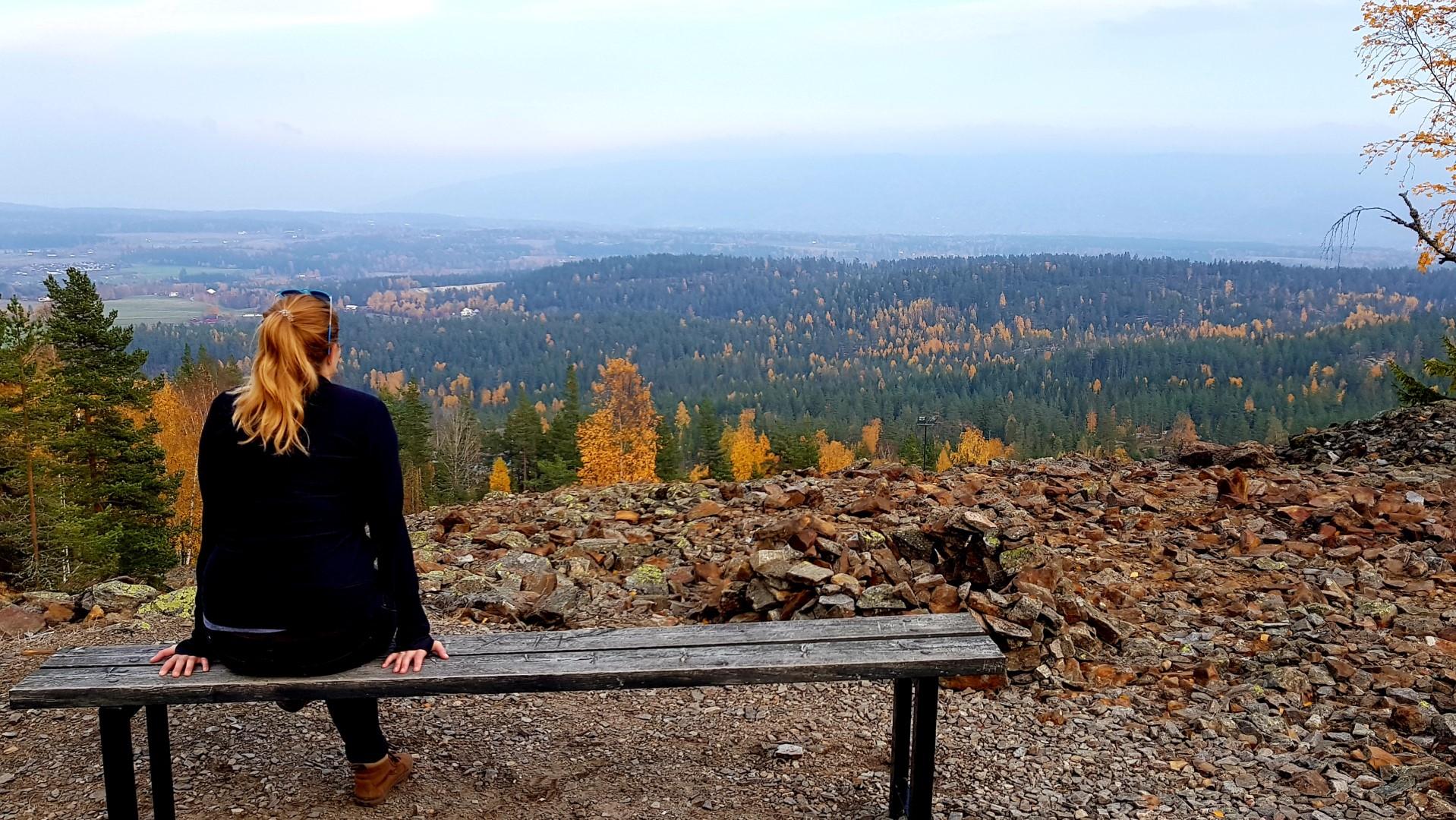Dziewczyna siedząca na ławce i patrząca na dolinę niedaleko Oslo.