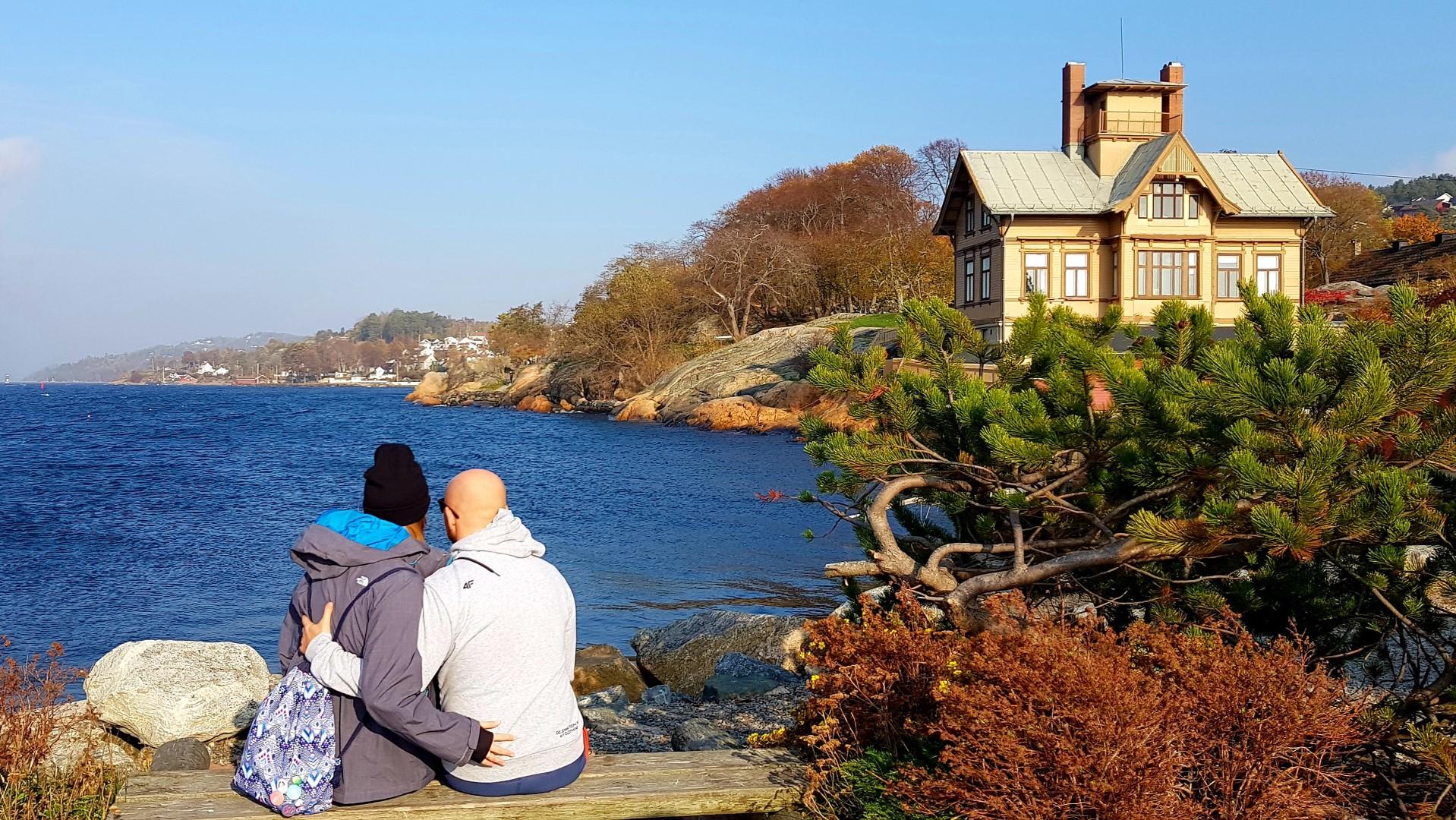 Para siedząc na łąwce. Obejmująca się i patrząca na zatokę w Drobak.