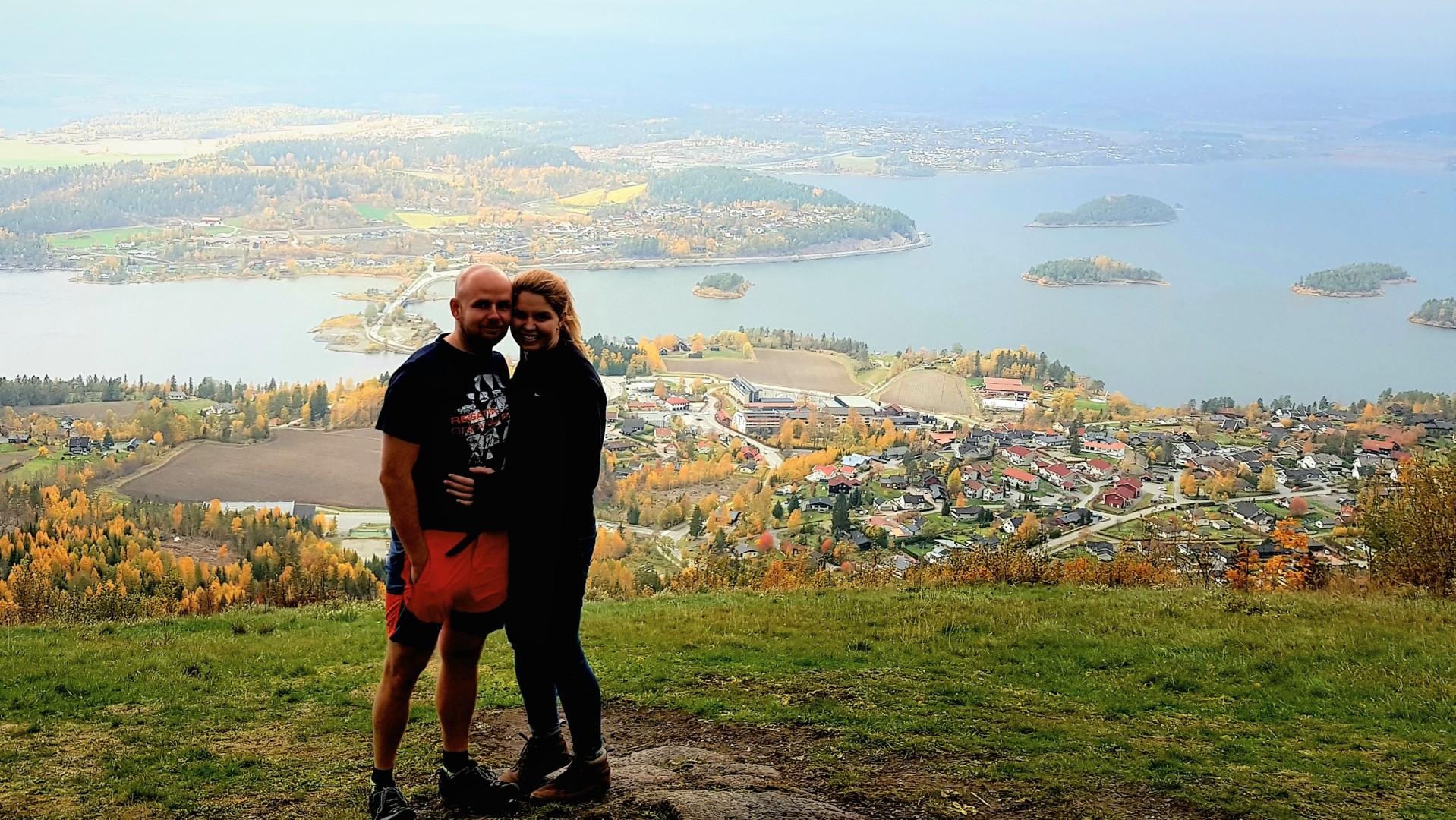 Para na tle wysepek niedaleko Oslo. W dole miasteczko skąpane w jesiennych kolorach.