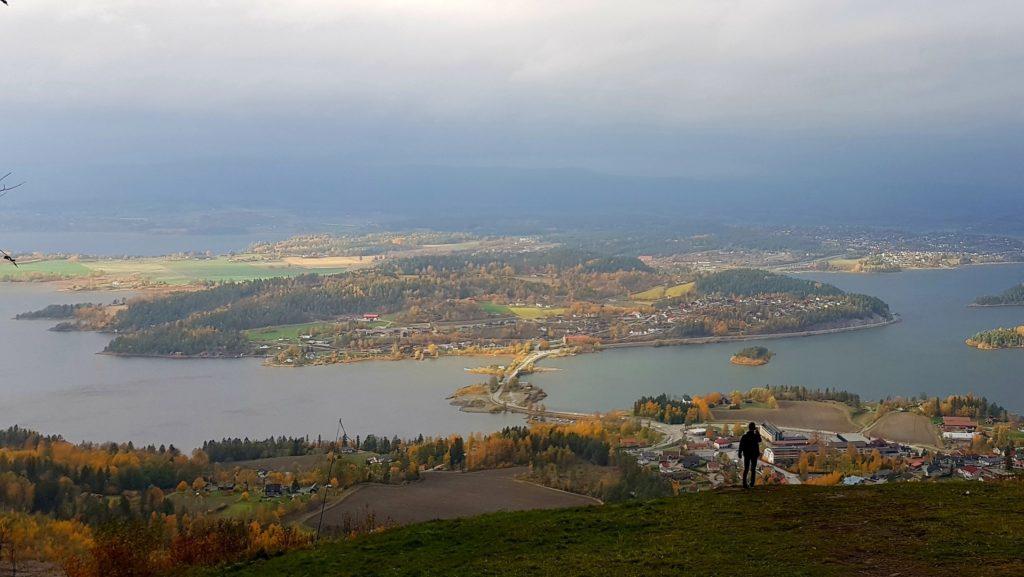 Człowiek na tle wysepek niedaleko Oslo. W dole miasteczko skąpane w jesiennych kolorach.