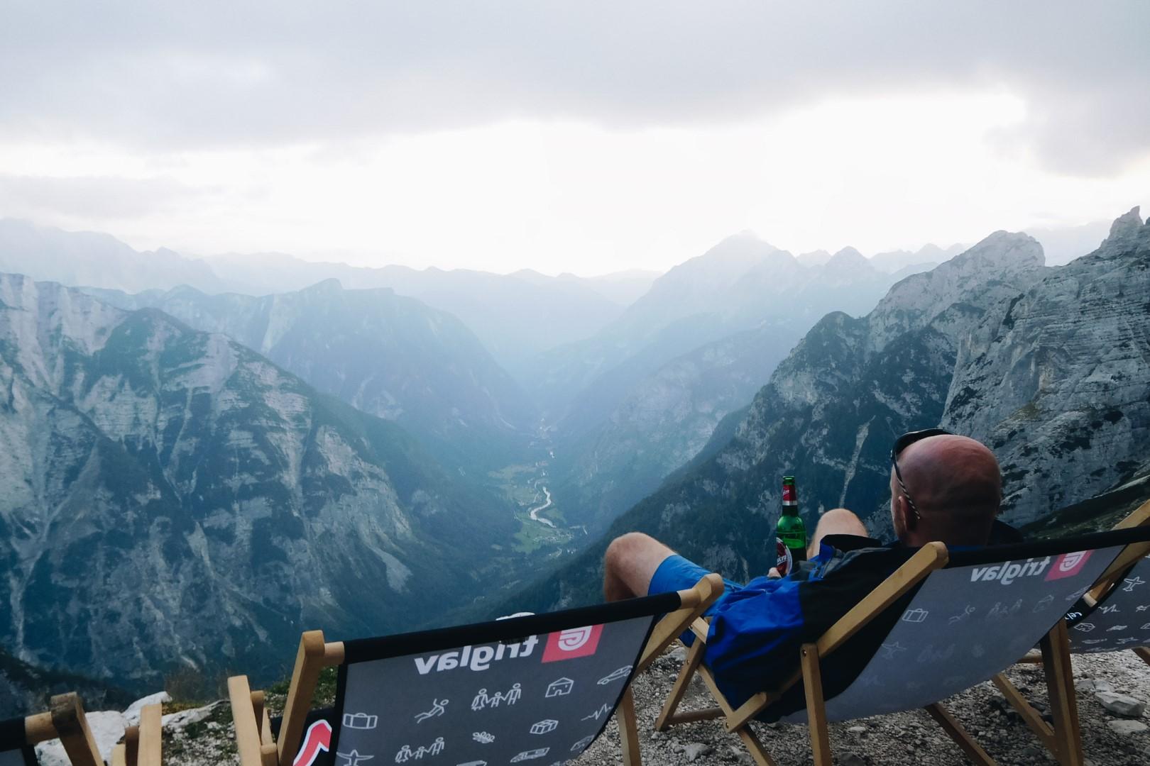 Mężczyzna z piwem leżący na leżaku, patrzący na Alpy Julijskie.