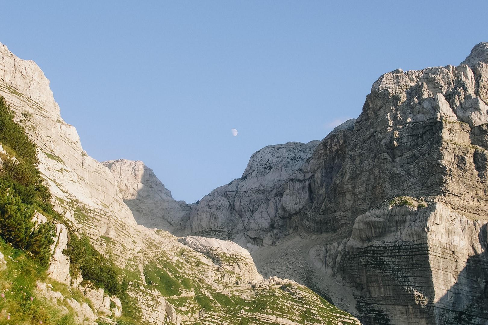 Widok na Alpy Julijskie ze szlaku na Triglav. Księżyc nad górami.
