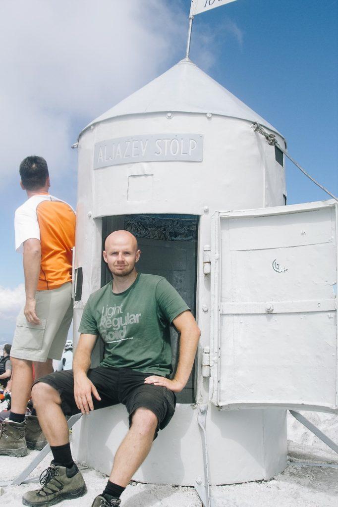 Mężczyzna siedzący na wierzchołku Triglava, schron na szczycie.