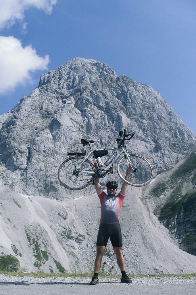 Mężczyzna trzymający w górze rower po wjeździe na Mangart.