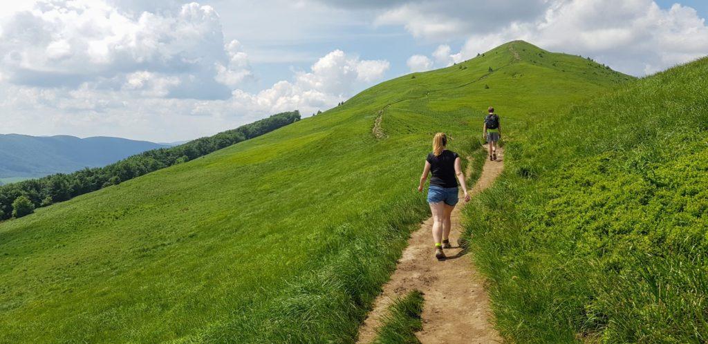 Dziewczyna idąca szlakiem w zielonych Bieszczadach.
