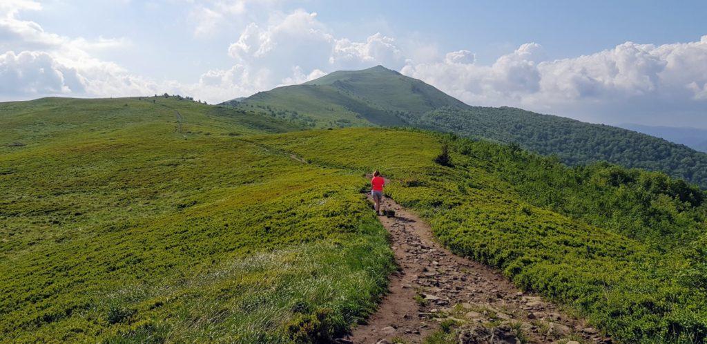 Samotna dziewczyna na bieszczadzkim szlaku. Zielone szczyty gór.