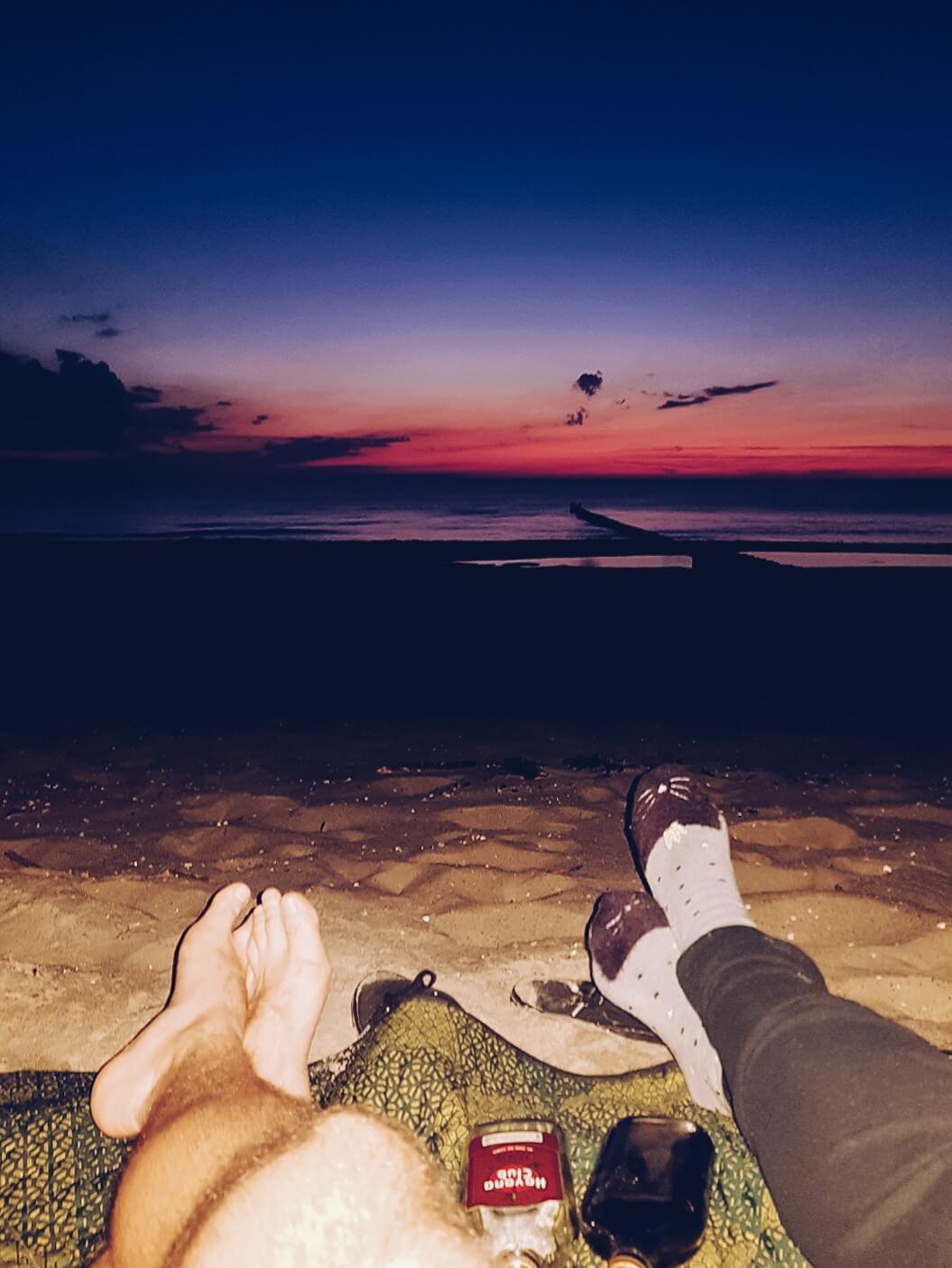 Para na plaży czekająca na wschód Słońca.