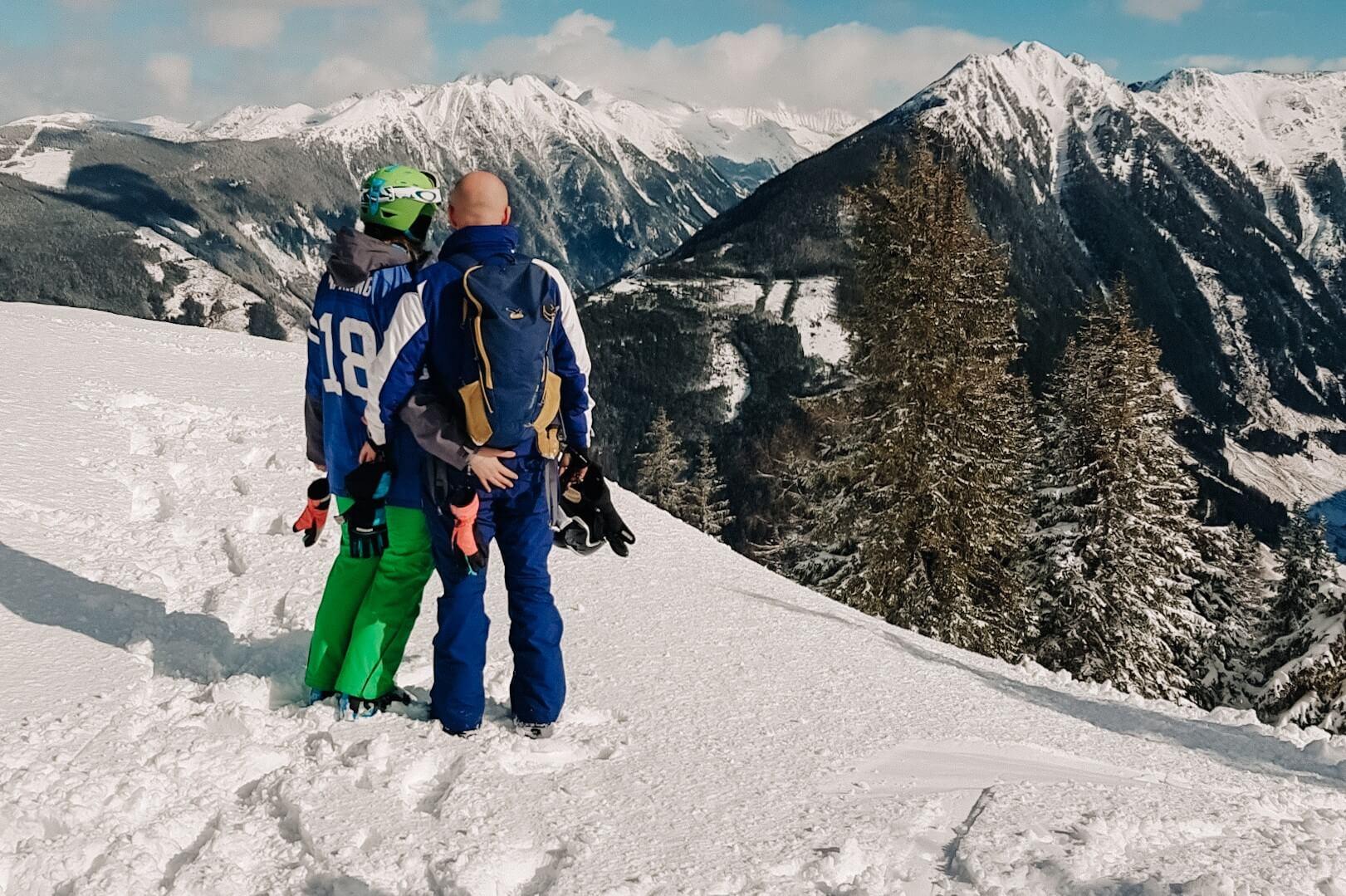 Para na stoku narciarskim patrząca na góry.