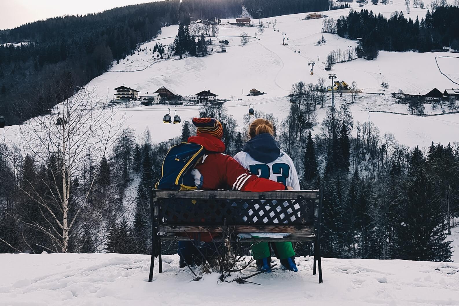 Para na ławce patrząca na stok narciarski.