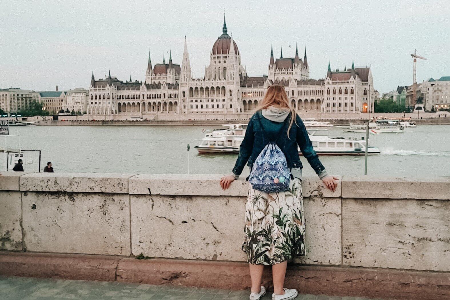 Dziewczyna nad brzegiem dunaju podziwiająca gmach parlamentu w Budapeszcie.