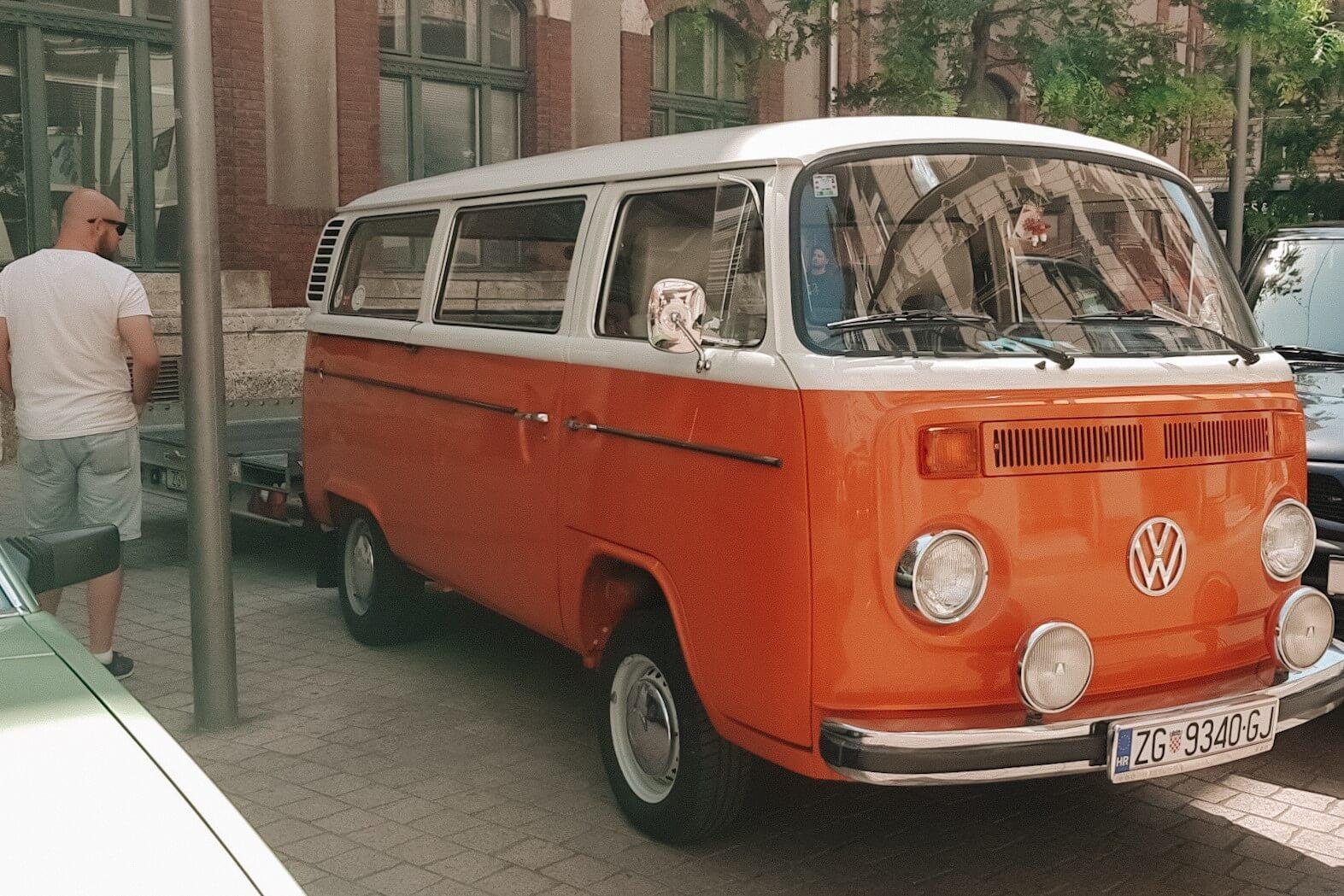 Mężsczyzna oglądający zabytkowy pomarańczowy samochód, VW Transporter T2