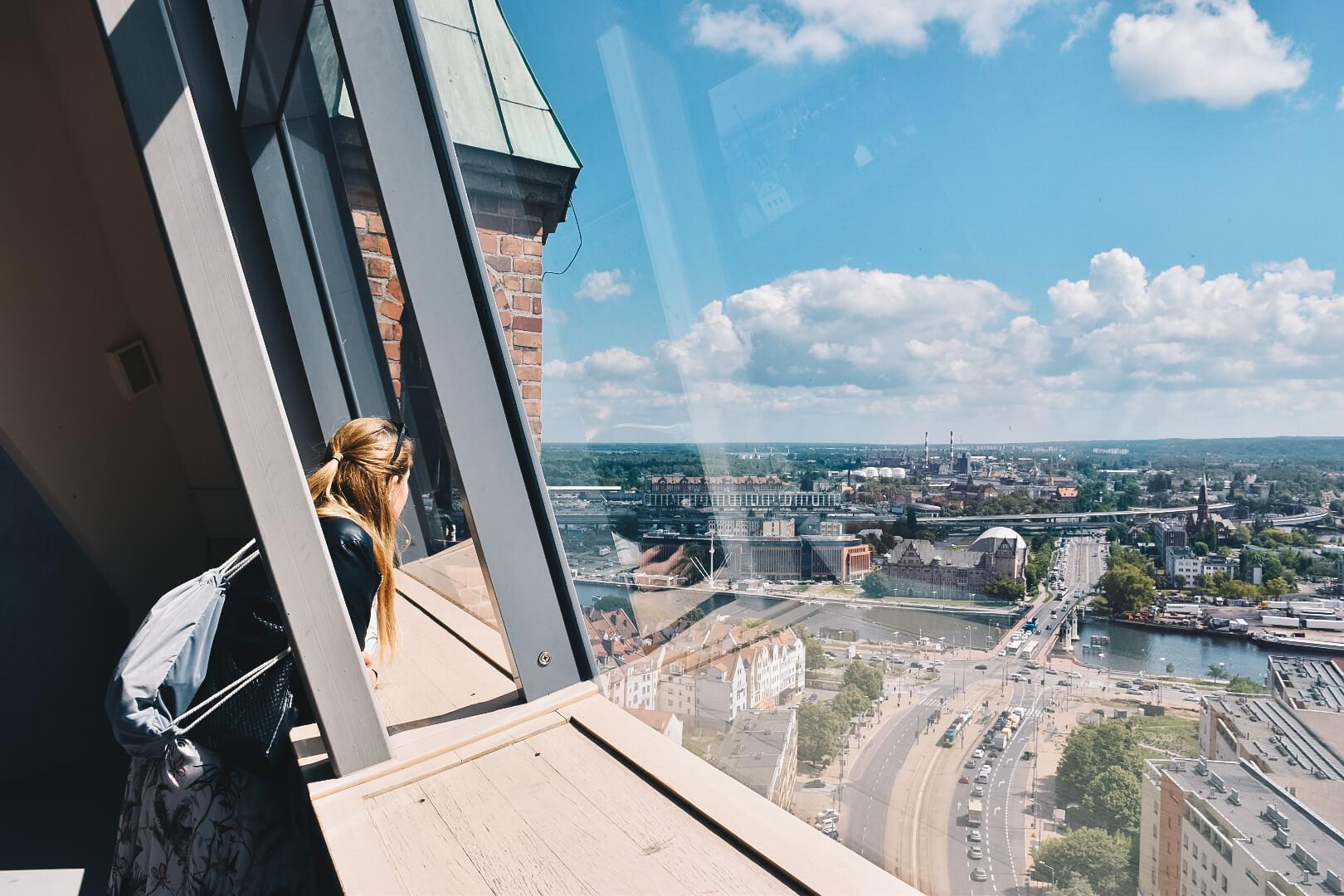 Dziewczyna patrząca z wieży widokowej na Szczecin.