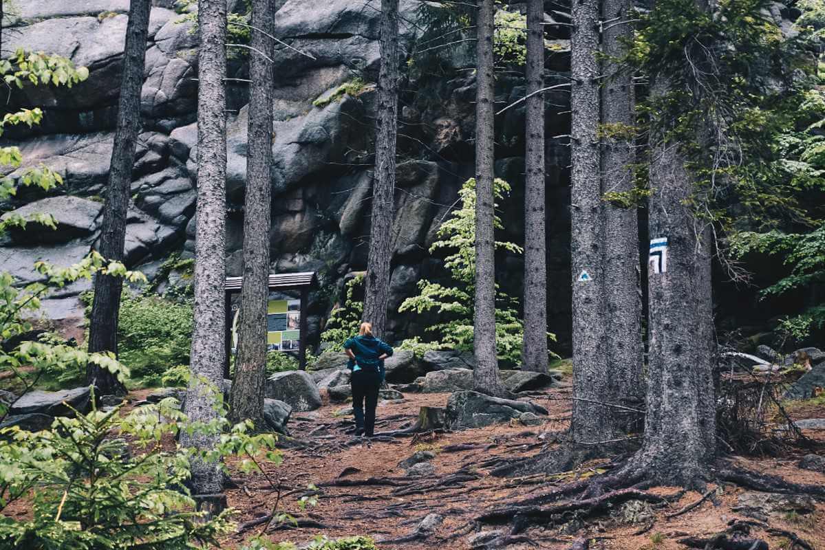 Rudawy Janowickie, Turystka stojąca pod wielkimi skałami.