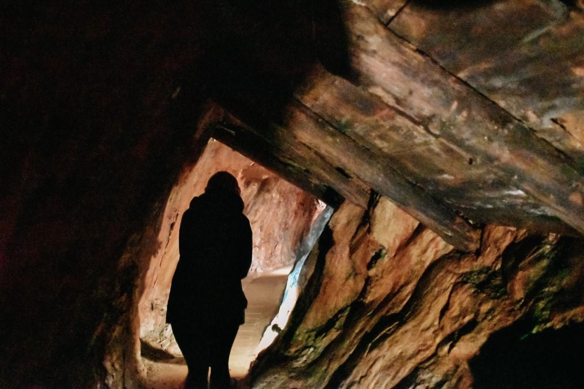 Dziewczyna przeciskająca się przez wąski tunel kopalni.