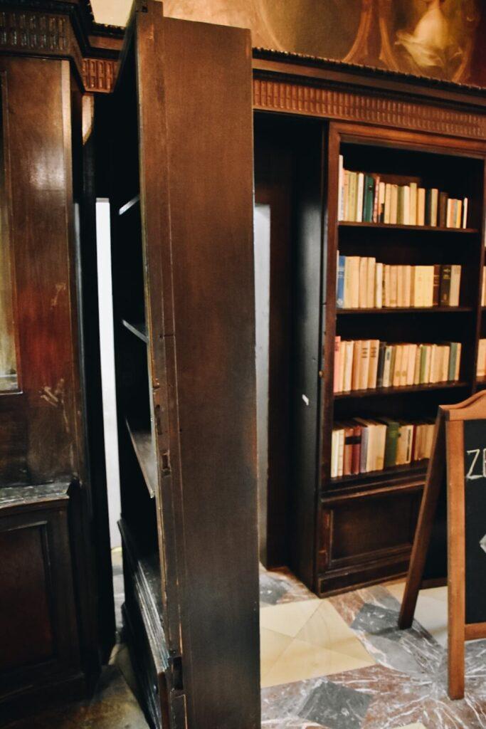 Tajne przejście w zamku za regałem z książkami.