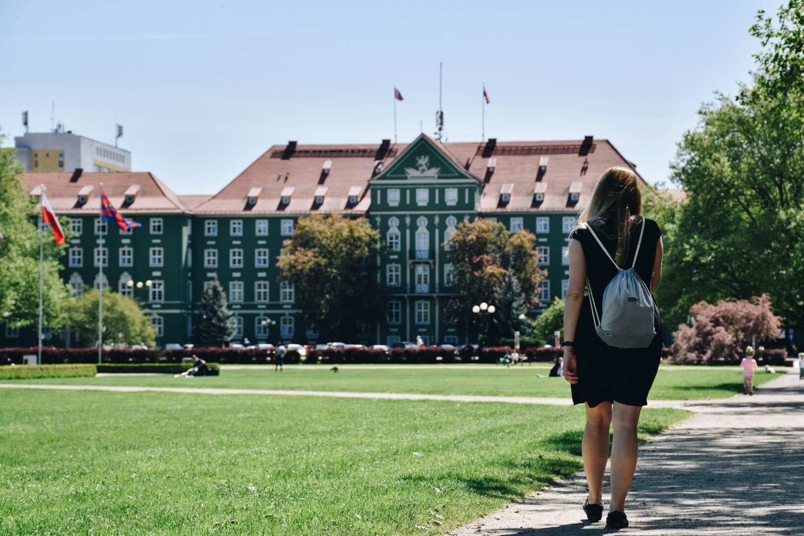 Dziewczyna w czarnej sukience spaceruje po Placu Jasne Błonia, Szczecin.