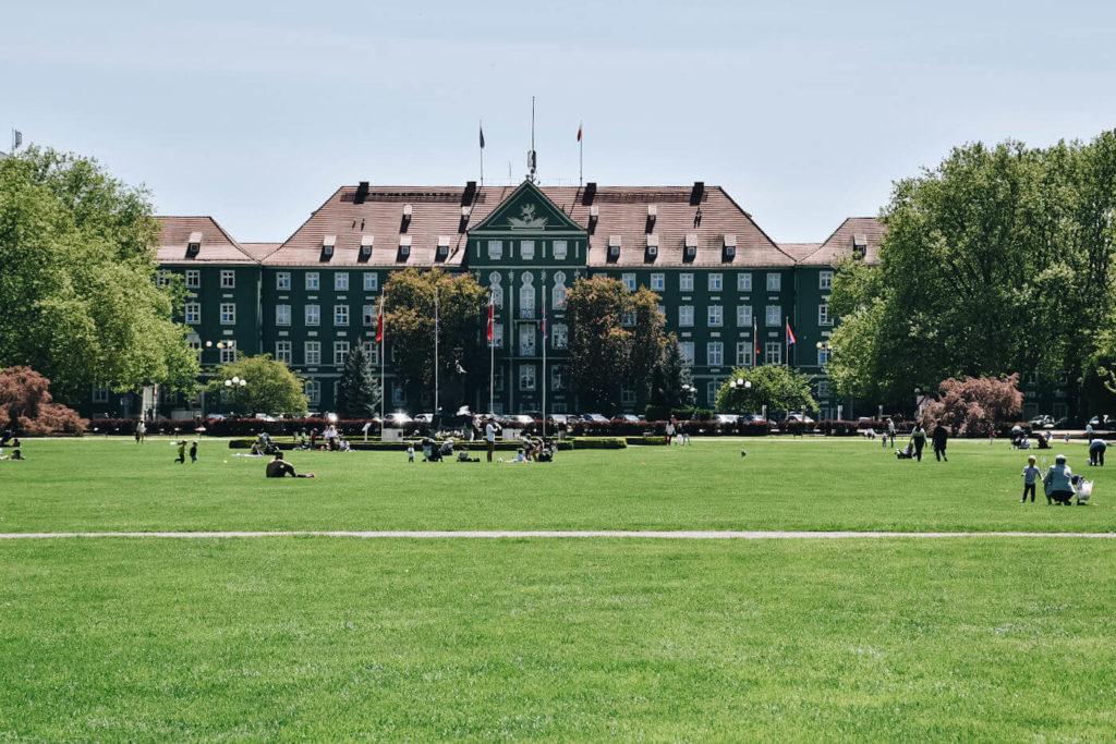 Ludzie wypoczywający na trawniku przez Urzędem Miasta w Szczecinie. Plac Jasne Błonia.