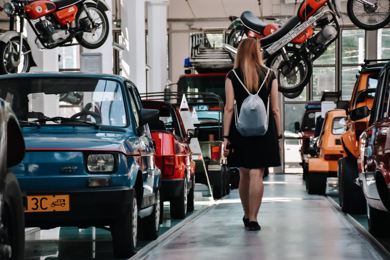 Dziewczyna w czarnej sukience przechadza się między starymi samochodami w Muzeum Techniki i Komunikacji Zajezdnia, Szczecin.