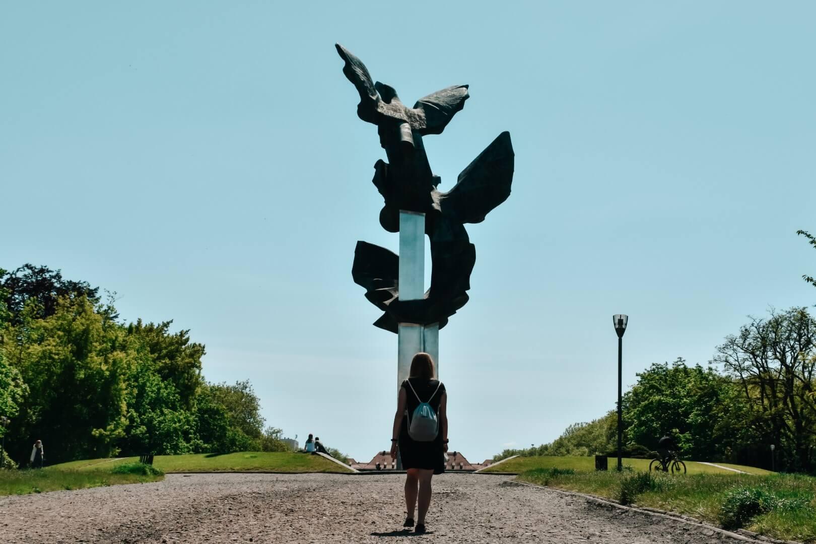 Dziewczyna w czarnej sukience z plecakiem spaceruje pod Pomnikiem Czynu Polaków Szczecin.