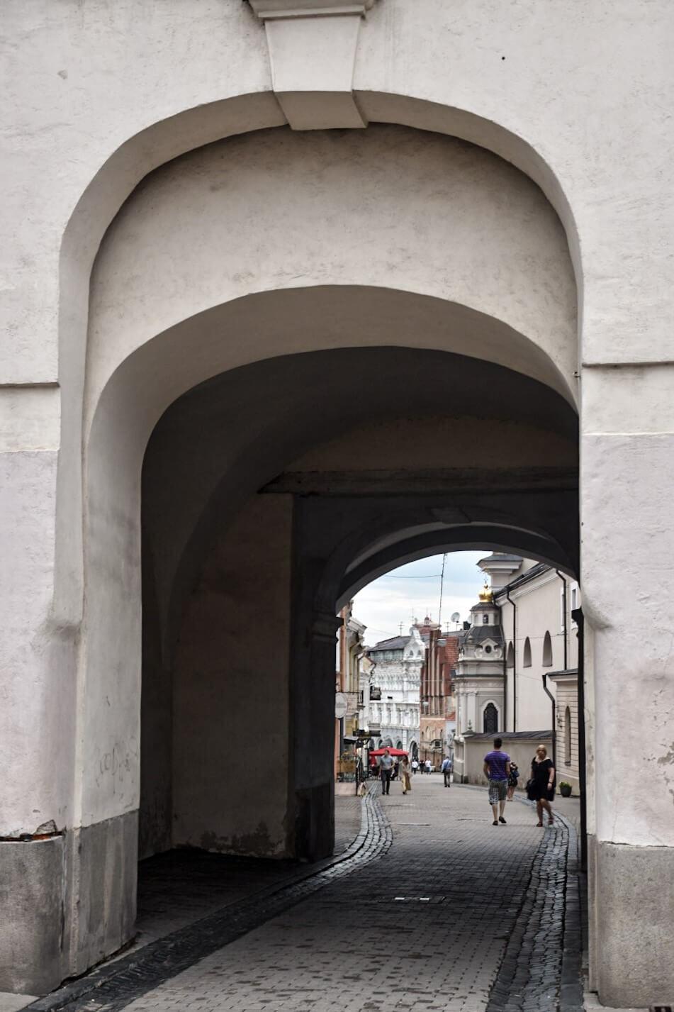 Turści spacerujący ulicą Wilna, widziani spod Ostrej Bramy.