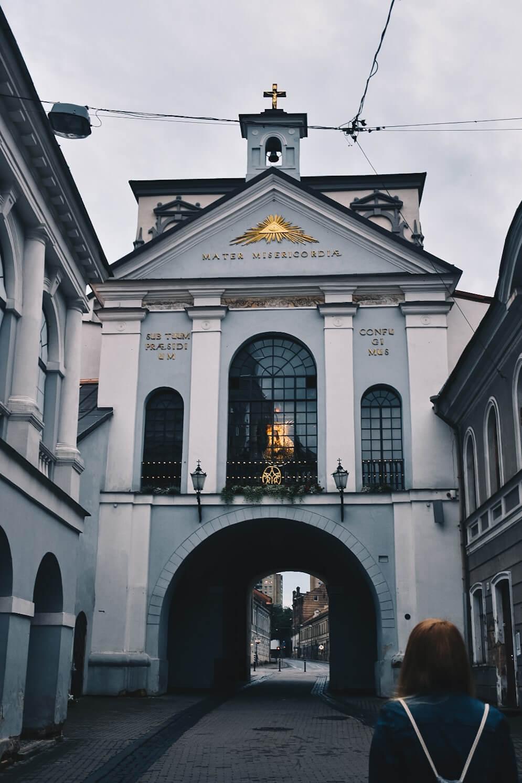 Dziewczyna patrząca na Ostrą Bramę w Wilnie.