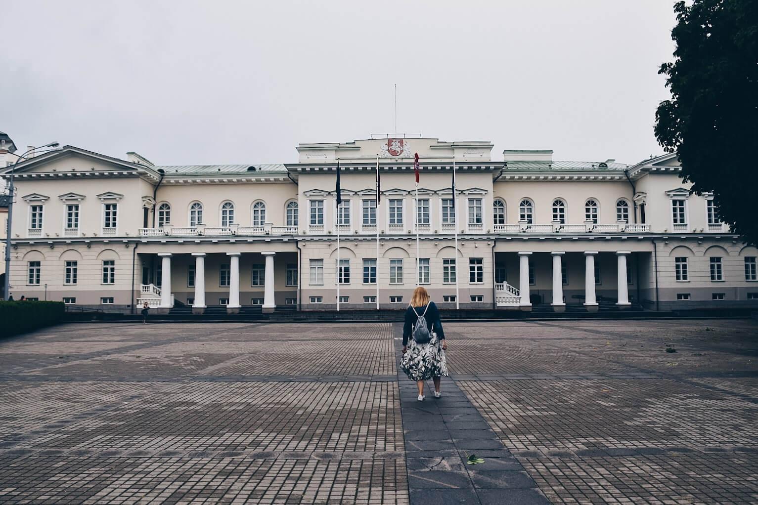 Dziewczyna w sukience przed Pałacem Prezydenckim w Wilnie.