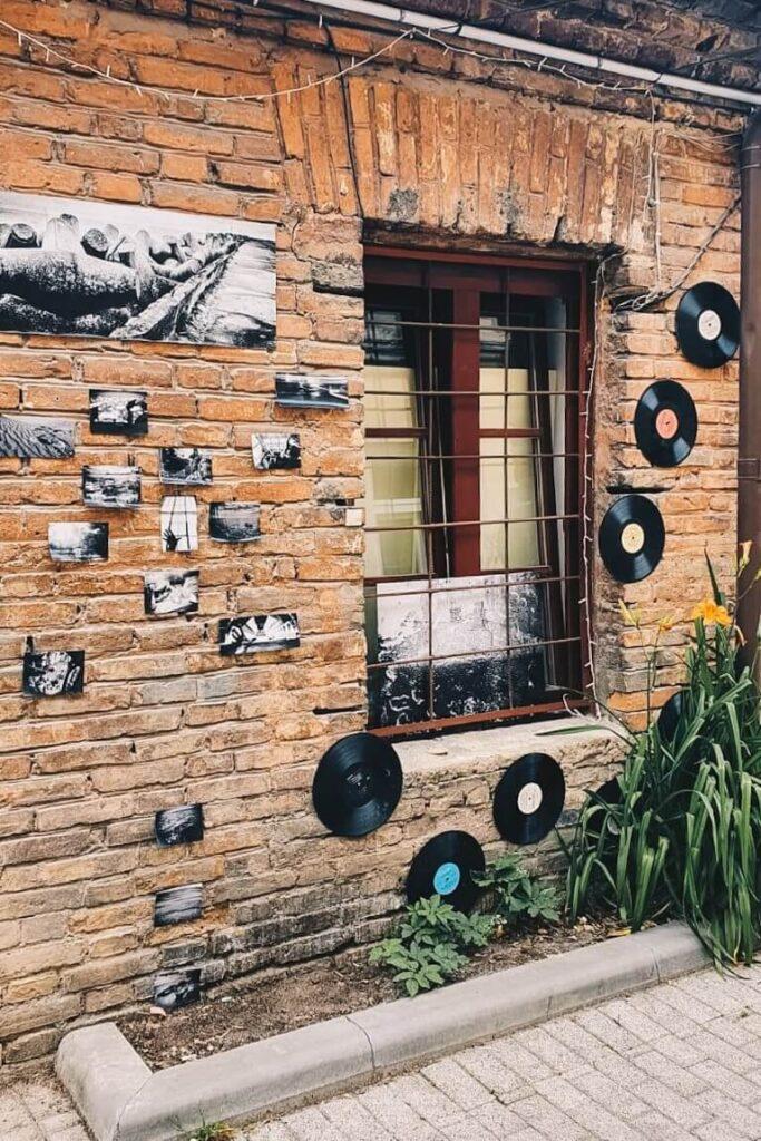 Winylowe płyty i zdjęcia na ścianie budynku w dzielnicy Zarzecze, Wilno.