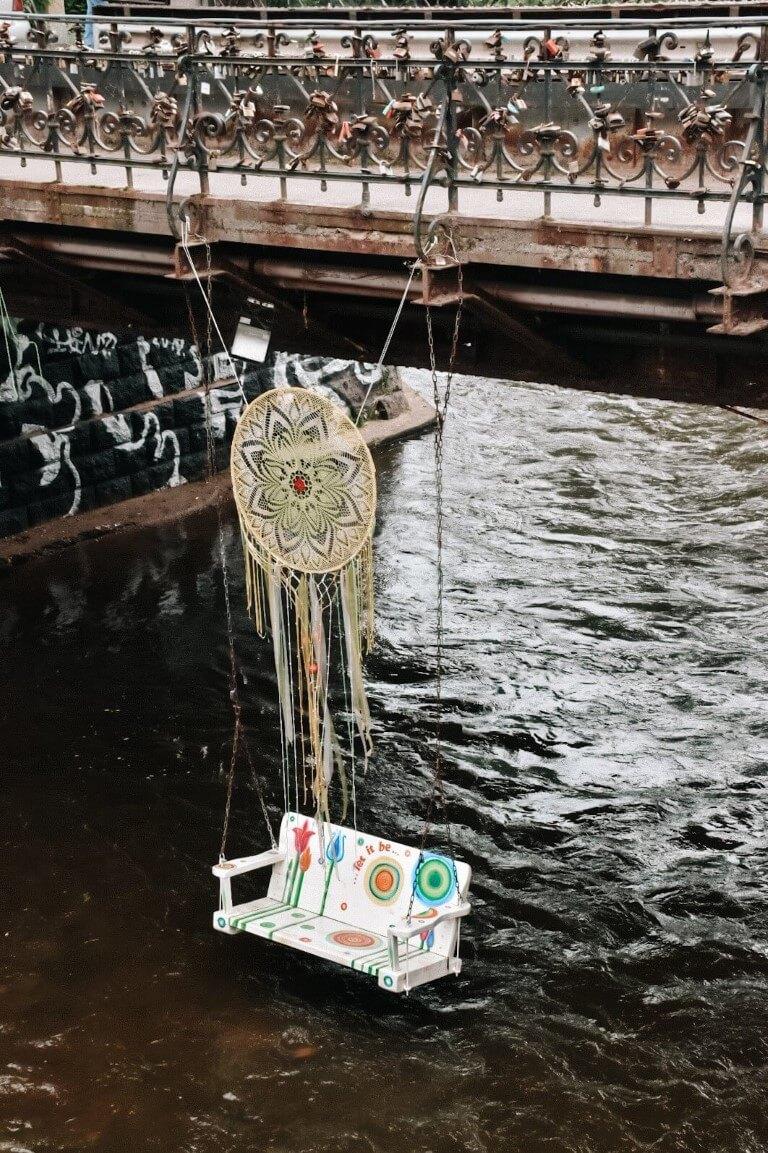 Huśtawka podwieszona nad woda, pod mostem w dzielnicy Zarzecze, Wilno.