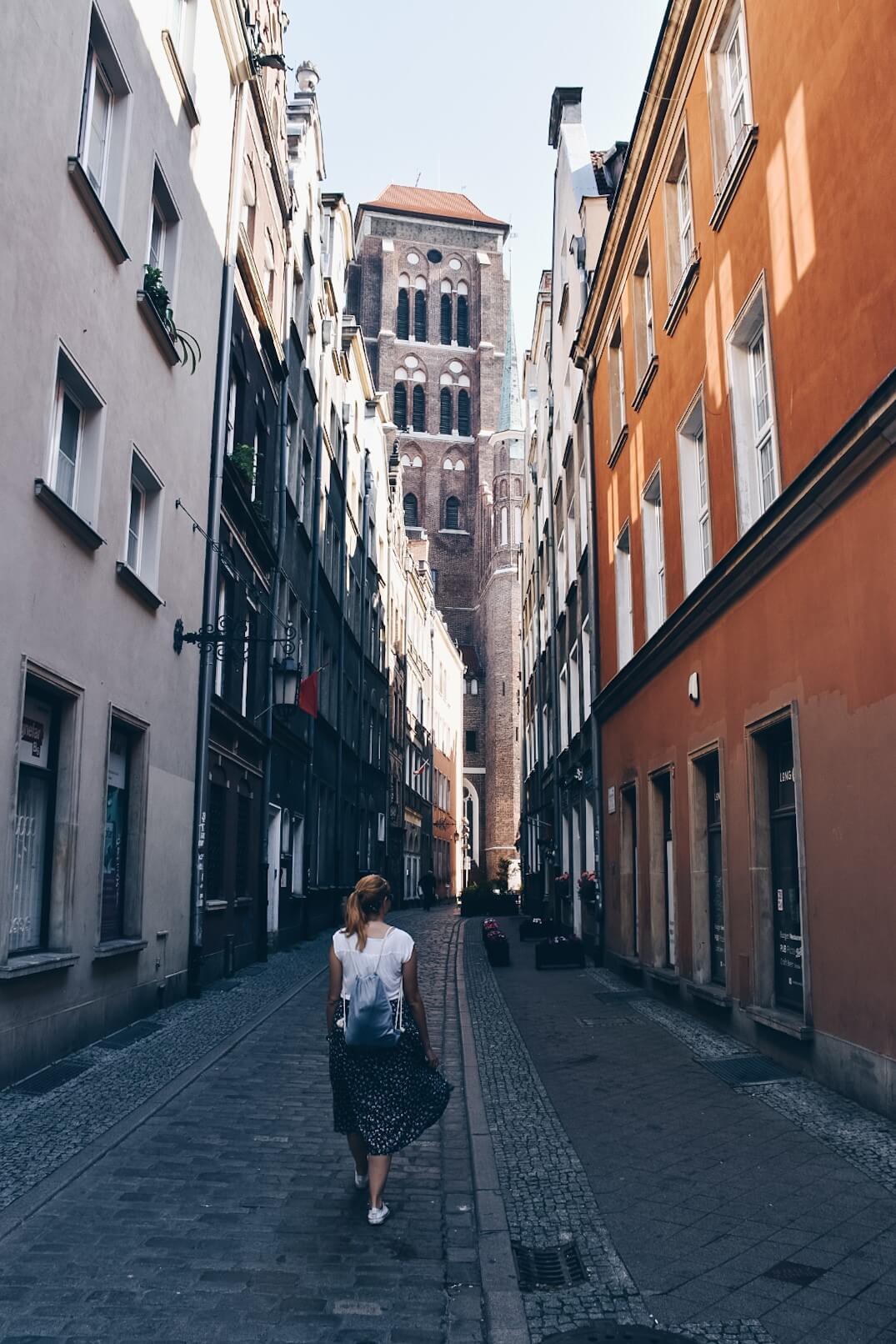 Wąska uliczka na gdańskiej starówce i wieża Bazyliki Mariackiej.