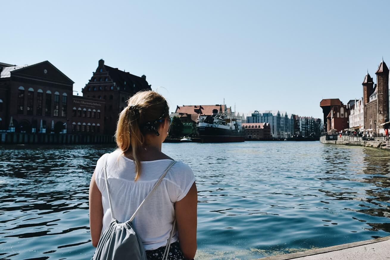 Turystka patrząca na Gdańsk na nabrzeżu Motławy.