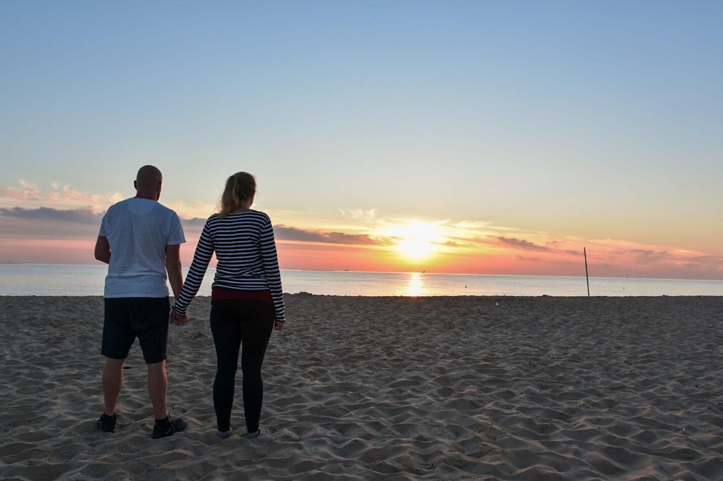 Prara trzymająca się za ręce na plaży o wschodzi Słońca.