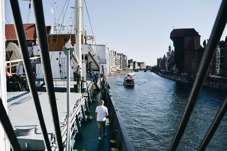Nabrzeże Motławy i turysta zwiedzający statek Sołdek.