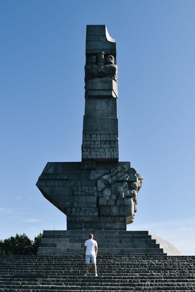 Turysta pod pomnikiem Obrońców wybrzeża na Westerplatte.